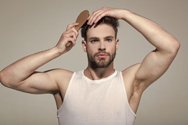 男は灰色の表面にヘアブラシで髪を磨く