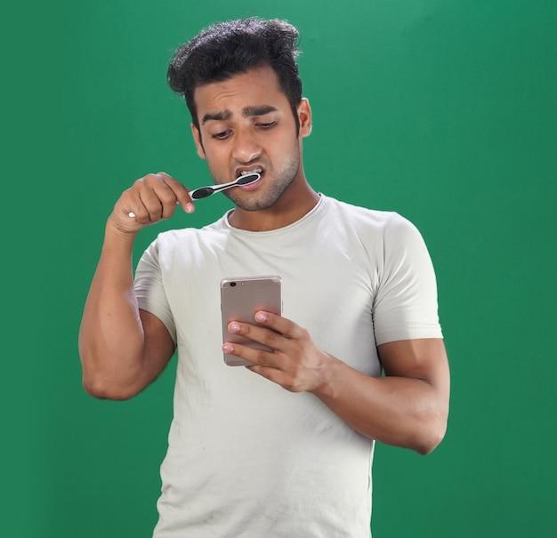 男は目覚めた後、朝に歯を磨き、携帯電話を使用します
