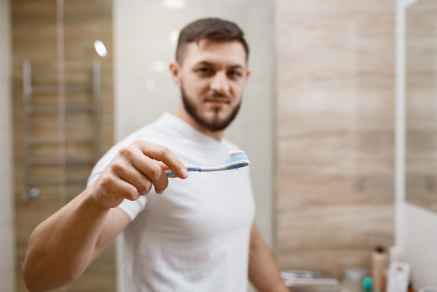 男はバスルームで歯を磨く