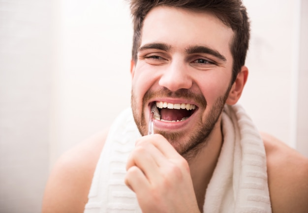Man brushing his teeth and looking in the mirror.