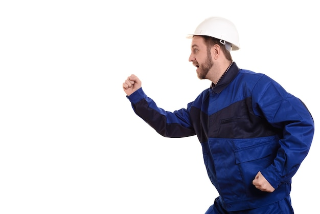 Man builder in hard hat and overalls runs for construction