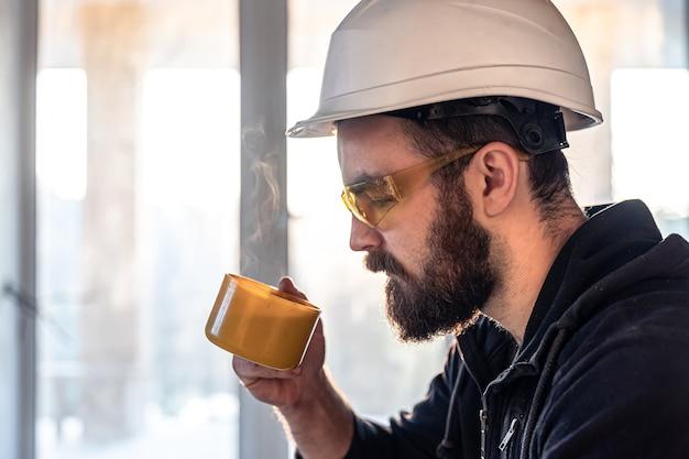 Un uomo costruttore in un casco e occhiali beve una bevanda calda