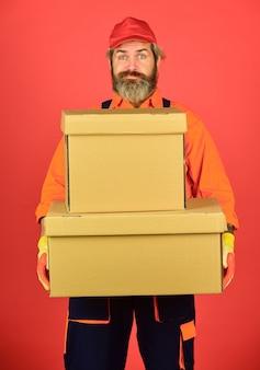 Строитель человек в боксах для хранения комбинезона. переезд в новую квартиру. картонная коробка счастливого человека. переноски ящиков внутри здания. распаковка движущихся ящиков. новый дом в день переезда. люблю там, где ты живешь.