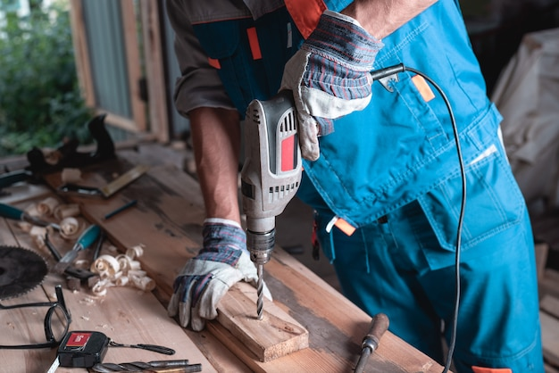 Строитель человек в комбинезоне и перчатках сверла деревянная доска крупным планом.