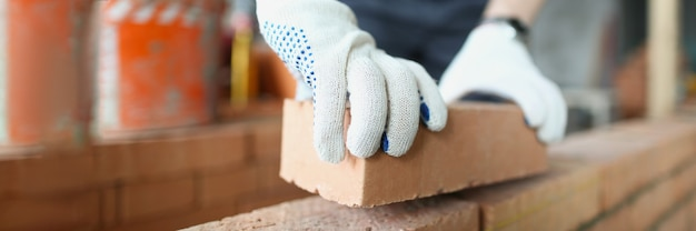 Строитель человека в защитных перчатках строит стену из кирпича крупным планом. концепция ремонта квартир
