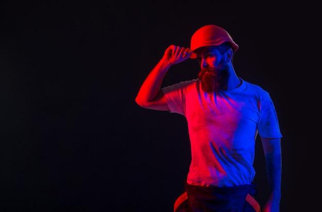 Строитель человек, промышленность, технологии, концепция строителя. архитектор-строитель, работает инженер-строитель. строители в каске, каске. бородатый рабочий мужчина с бородой в строительном шлеме или каске. копировать пространство