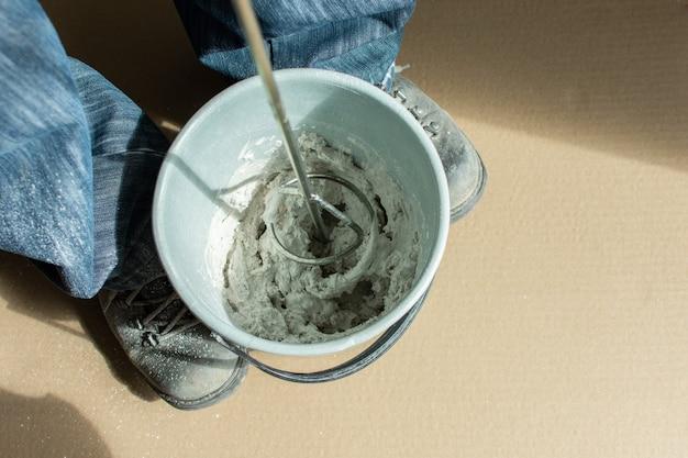 男ビルダーはバケツに石膏パテを混ぜます