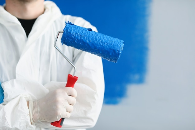 Ремонтник строитель человек держит ролик с синей краской в его руках крупным планом