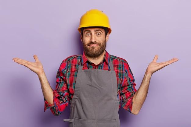 Man builder wears building helmet and apron, spreads hands in confusing gesture