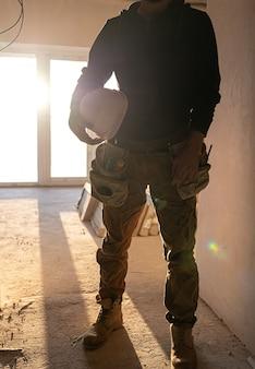 Un uomo costruttore con un casco in mano