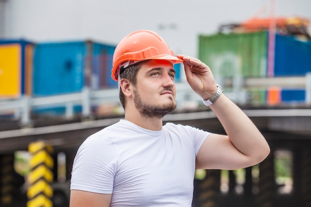 Man the builder working foreman in the helmet to ensure safety on the construction site. worker, engineer, foreman, architect.