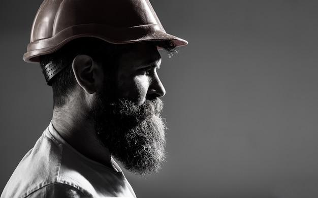 남자 빌더, 산업. 헬멧 또는 하드 모자를 구축에 수염을 가진 수염 난된 남자 노동자. 초상화 빌더, 토목 기사 근무. 헬멧에 하드 모자, 감독 또는 수리공에 작성기