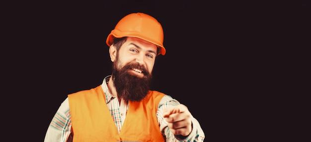 Человек-строитель, промышленность. строитель в каске, прораб или ремонтник в каске. бородатый рабочий мужчина с бородой в строительном шлеме или каске. портрет улыбающегося строителя. лицо крупным планом.
