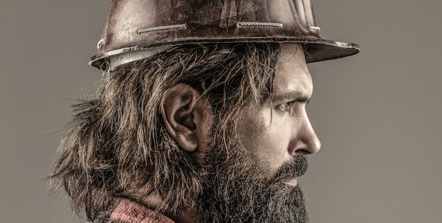 남자 건축업자, 산업. 헬멧에 단단한 모자, 감독 또는 수리공을 쓴 빌더. 건물, 산업, 기술 - 작성기 개념입니다. 헬멧이나 단단한 모자를 쓰고 있는 수염이 난 남자 노동자.