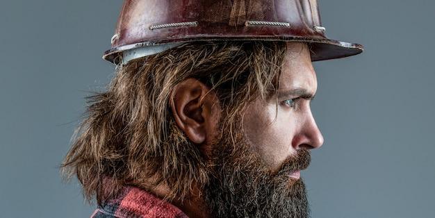 남자 건축업자, 산업. 헬멧에 단단한 모자, 감독 또는 수리공을 쓴 빌더. 건물, 산업, 기술-빌더 개념입니다. 헬멧이나 단단한 모자를 쓰고 있는 수염난 남자 노동자.