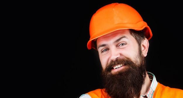 Человек-строитель, промышленность. строитель в каске, прораб или ремонтник в каске. портрет улыбающегося строителя.