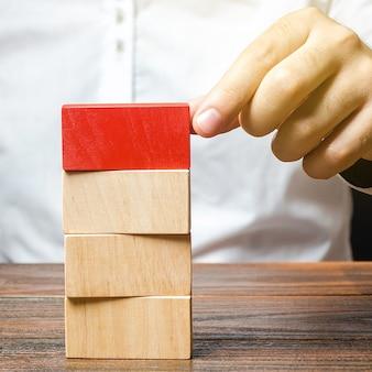 Человек строит башню из блоков