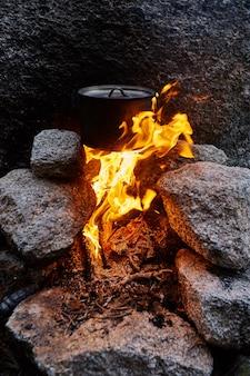 人は自然の森の中にキャンプファイヤーを建てました。キャンプファイヤーの上で鍋で料理をしながら、森の山で生き残ります。焚き火で沸騰したお湯をカモフラージュした男が生き残る。石でできた暖炉