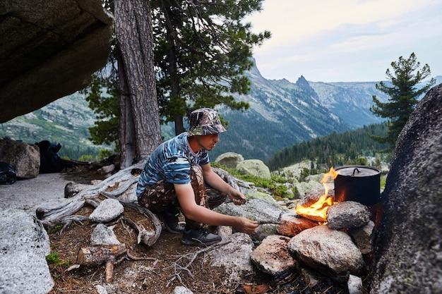 男は自然の森の中でキャンプファイヤーを建てました