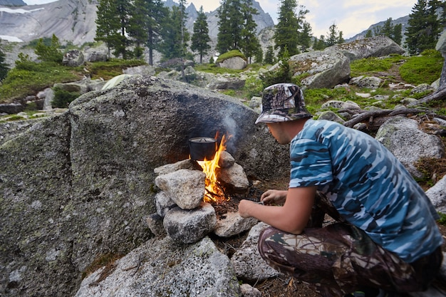 Man built a campfire in the woods in nature. survive in the mountains in the forest, cooking in a pot pan over a campfire. man in camouflage boiling water on bonfire, survive. fireplace made of stones