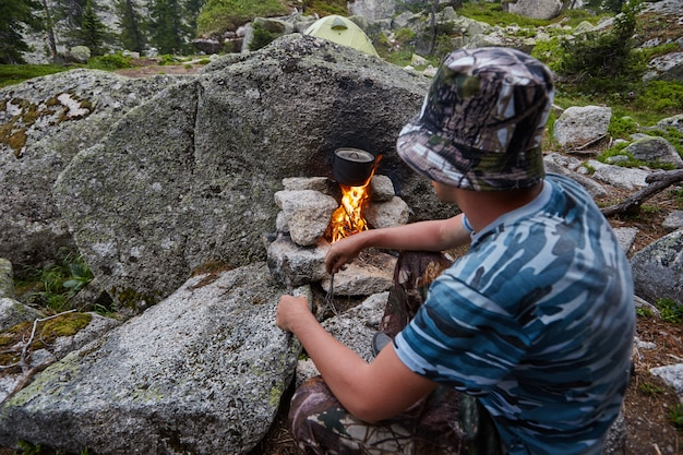 Man built a campfire in the woods in nature. survive in the mountains in the forest, cooking in a pot