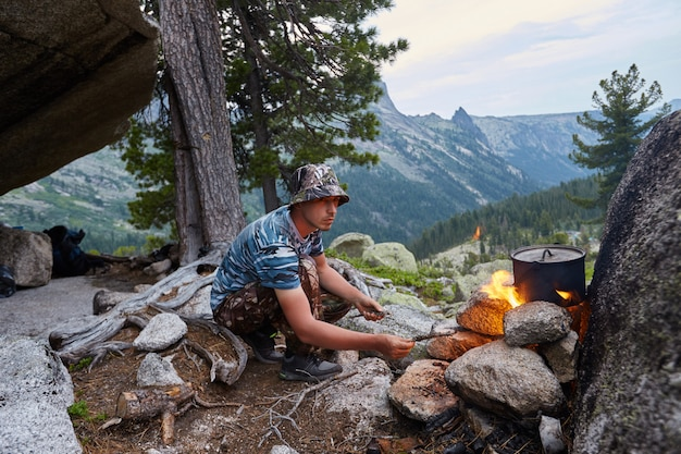 Man built a campfire in woods in nature. survive