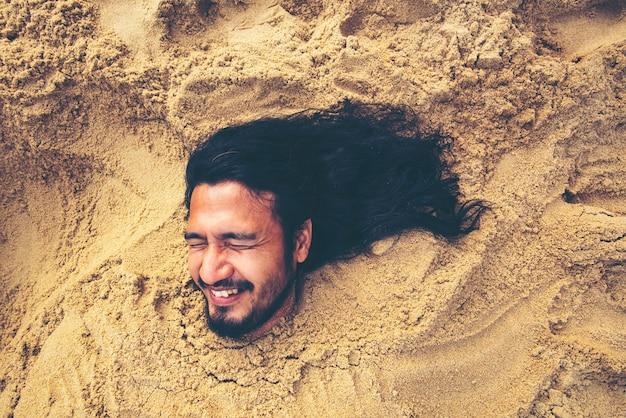 Человек похоронен в песке на пляже. концепция счастья, отдых, все в порядке.