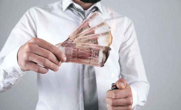 ロシアルーブル紙幣を燃やす男。