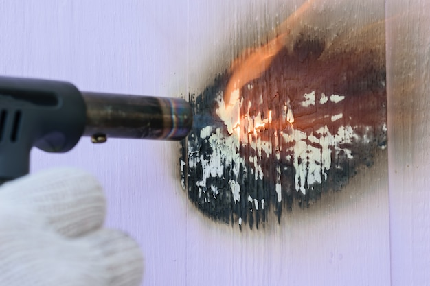 A man burns a gas burner boards painted in purple.