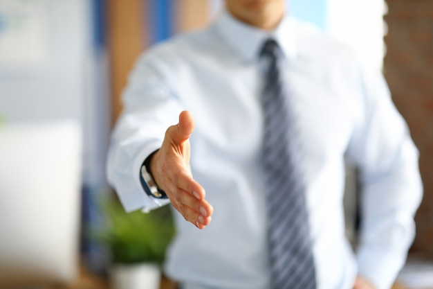 Man in business clothes holds out his hand for a greeting. office employee meets colleagues