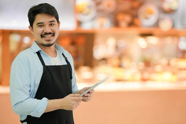 Владелец бизнеса мужчина держит планшет для проверки заказа от клиента
