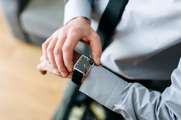 A man in a business suit checking a wrist watch on his hand
