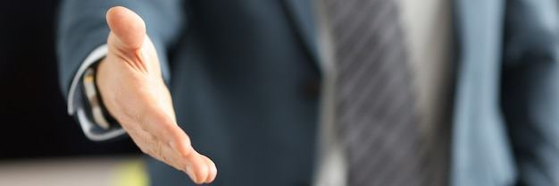 Man in business suit giving his hand for handshake closeup business deals concept