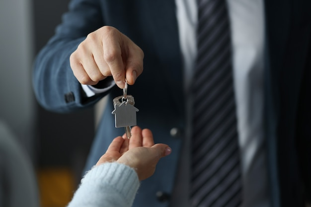Man in business suit hands overing house keys to woman closeup