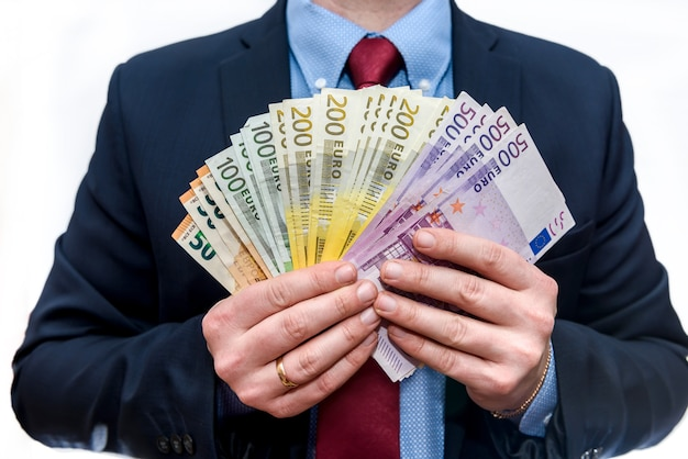 Man in business suit holds euro denominations