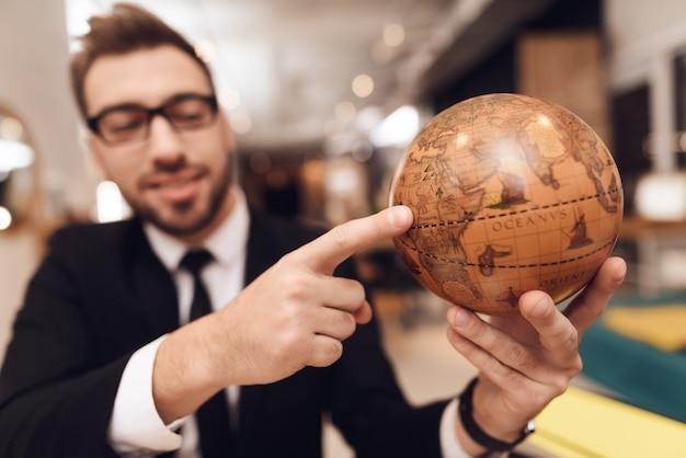 A man in a business suit is holding a globe in his hands.