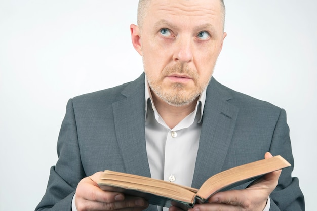 Man in a business suit is reading the bible.