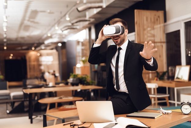 A man in a business suit looking into a virtual reality.