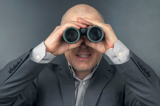 Man in a business suit looks through binoculars