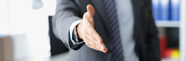 Man in business suit stretches out hand for handshake