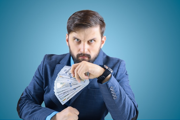 A man in a business suit with banknotes in his hands clenched his fist and looks viciously straight