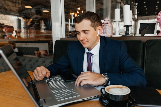 A man in a business suit works on a laptop in a cafe. businessman with laptop.
