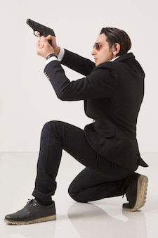 Man in business suite and gun on white background, shooting and sitting on white background