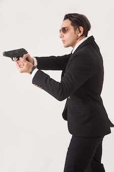 Man in business suite and gun on white background