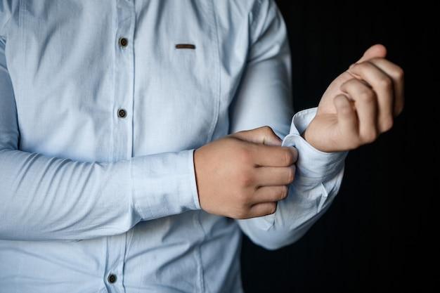 흰색 드레스 셔츠의 소매에 단추를 채우는 남자 사업가