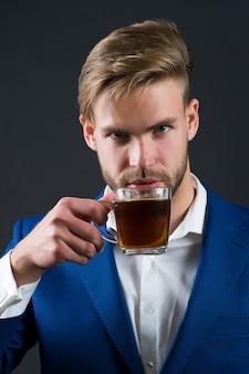 男性実業家は青いジャケット、灰色の背景に白いシャツでお茶を飲みます。オフィスのコーヒーブレイクのコンセプト。ビジネスと起業家精神。
