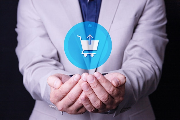 A man, a businessman holds a shopping basket logo in his palms.