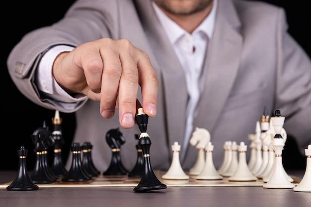 A man, a businessman plays chess, makes a move a black piece