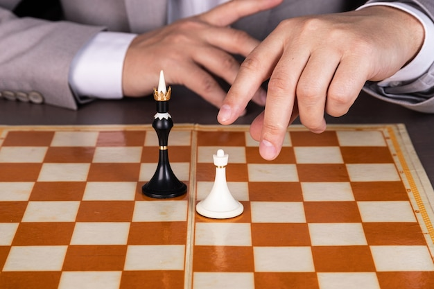 A man, a businessman, plays chess, makes a move with a white piece