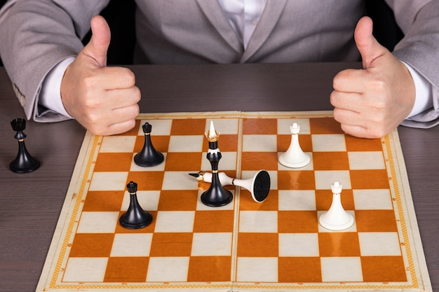 A man, a businessman plays with chess pieces, one piece beats another